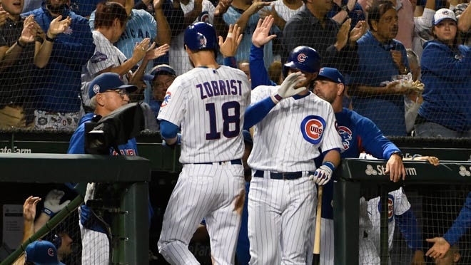 Chicago Cubs' Ben Zobrist (18) is greeted by his teammates after scoring against the Milwaukee Brewers during the second inning of a baseball game, Tuesday, Sept. 11, 2018, in Chicago. (AP Photo/David Banks)