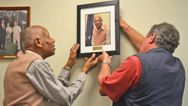 Benjamin Duncan (left) and then-mayor Edward Lemon (right) hang a photo of Duncan in the city council chambers on Dec. 4, 2017, which was Duncan's last meeting as a city councilman.