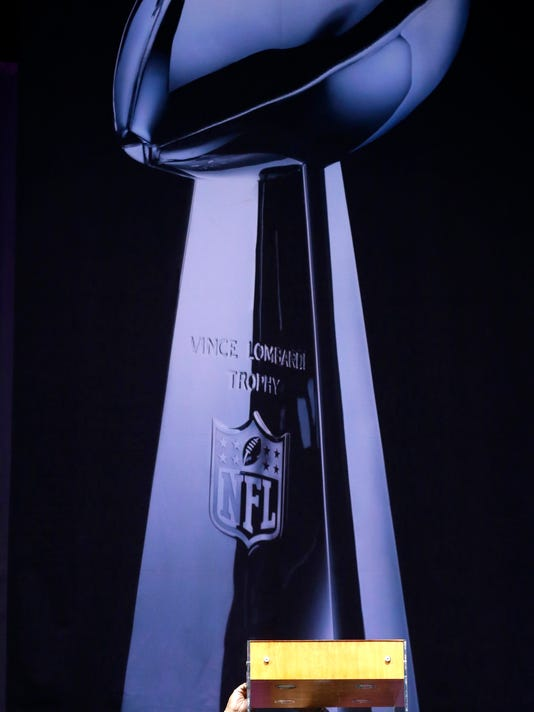 An NFL worker secures the Vince Lombardi Trophy in a case after it was delivered at the NFL Experience in preparation for Super Bowl XLIX Saturday, Jan. 24, 2015, in Phoenix. The New England Patriots face the Seattle Seahawks in Super Bowl XLIX on Sunday, Feb. 1, 2015, in Glendale, Ariz. (AP Photo/Charlie Riedel)