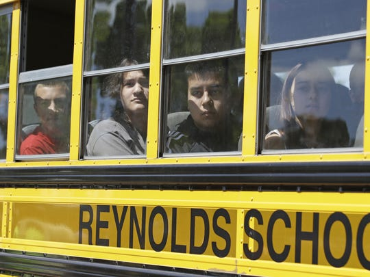 Students look for family members after arriving at a shopping center parking lot in Wood Village after a shooting at Reynolds High School Tuesday.  AP Students look for family members after arriving at a shopping center parking lot in Wood Village, Ore., after a shooting at Reynolds High School Tuesday, June 10, 2014, in nearby Troutdale. A gunman killed a student at the high school east of Portland Tuesday and the shooter is also dead, police said..  (AP Photo/Rick Bowmer)
