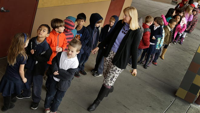 First-grade teacher Lynda Jensen walks with her class of 30 children at Willow Glenn Elementary School in San Jose, Calif., in July. Classes in California's public schools are getting bigger.