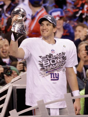 New York Giants quarterback Eli Manning holds the Vince Lombardi Trophy after the NFL Super Bowl XLVI football game against the New England Patriots, Sunday, Feb. 5, 2012, in Indianapolis. The Giants won 21-17. (AP Photo/Charlie Riedel)