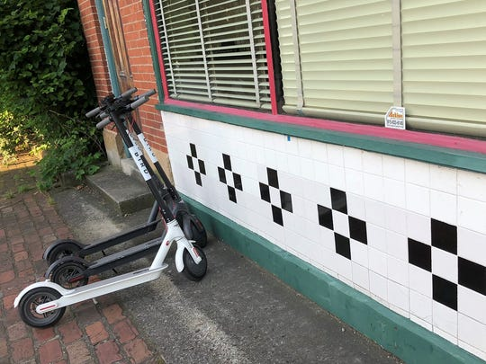 Two Bird scooters are stationed outside the old Mad