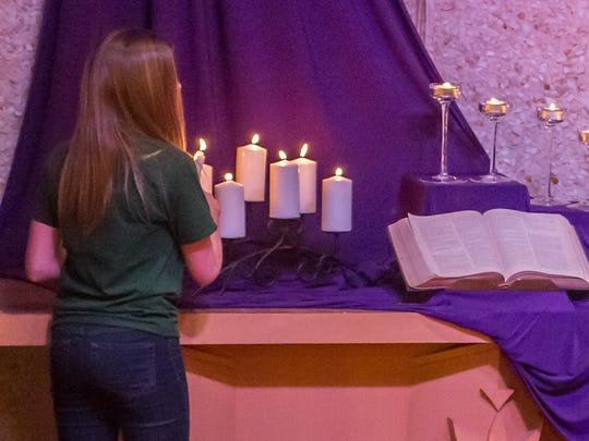 Harper Creek Middle School student Delaney Evans lights a candle for her classmate Abigail Kopf at a community prayer service at Chapel Hill United Methodist Church on Thursday. Kopf, 14, is still in critical condition at Bronson Methodist Hospital in Kalamazoo.