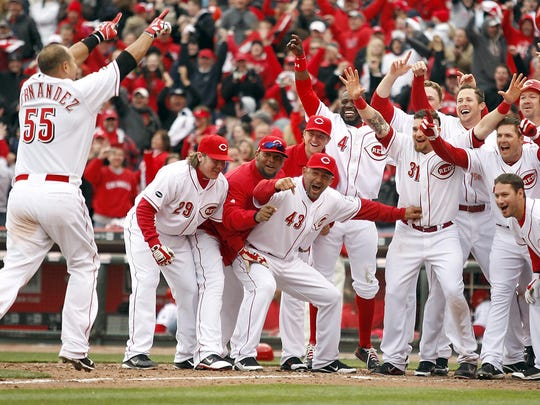Ramon Hernandez greets his teammates after he hit a three-run home run in the bottom of the 9th inning during Opening Day 2011. The Reds beat Brewers 7-6.