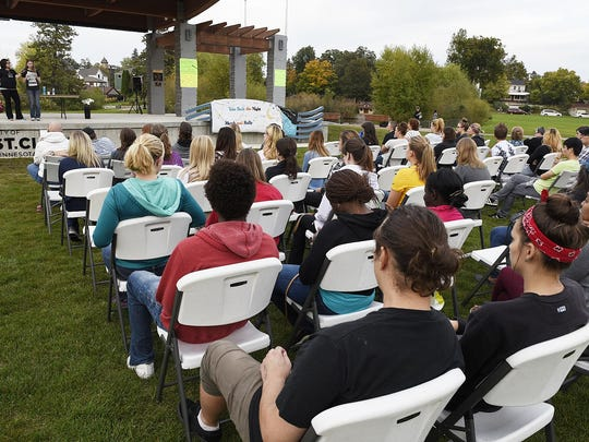People gather to listen to Rebecca Kotz, human trafficking service coordinator at the Central Minnesota Sexual Assault Center, as she speaks about domestic violence, sexual violence and human trafficking during the Central Minnesota Take Back the Night on Thursday in Eastman Park near Lake George.