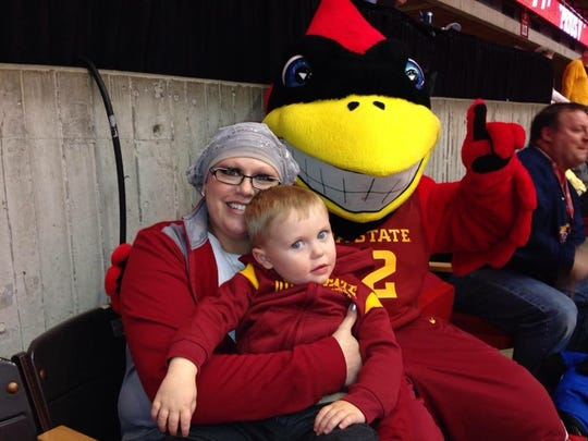 Melissa Grossman and her son Myles hang out with Cy at an Iowa State basketball game.