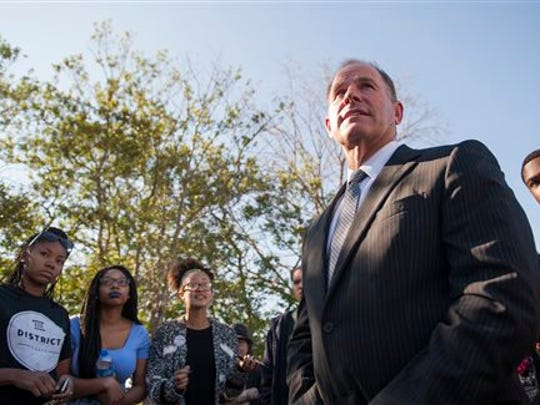 In a Tuesday, Nov. 3, 2015 photo, University of Missouri President Tim Wolfe speaks with members of Concerned Student 1950 senior Abigail Hollis, from left, senior DeShaunya Ware and junior Shelbey Parnell as they call for Wolfe's resignation outside University Hall on the University of Missouri campus, in Columbia, Mo. Long-simmering protests at the University of Missouri over matters of race and discrimination got a boost over the weekend when at least 30 black football players announced they will not participate in team activities until the university system's president is removed.