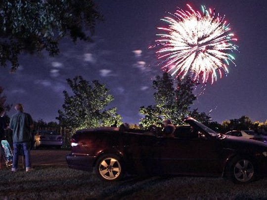 Randy and Tricia Travis of Anderson watch Zambelli Fireworks explode in the air from their car along Camson Road at the 17th annual Celebrate Anderson concert at the Civic Center of Anderson in 2013.
