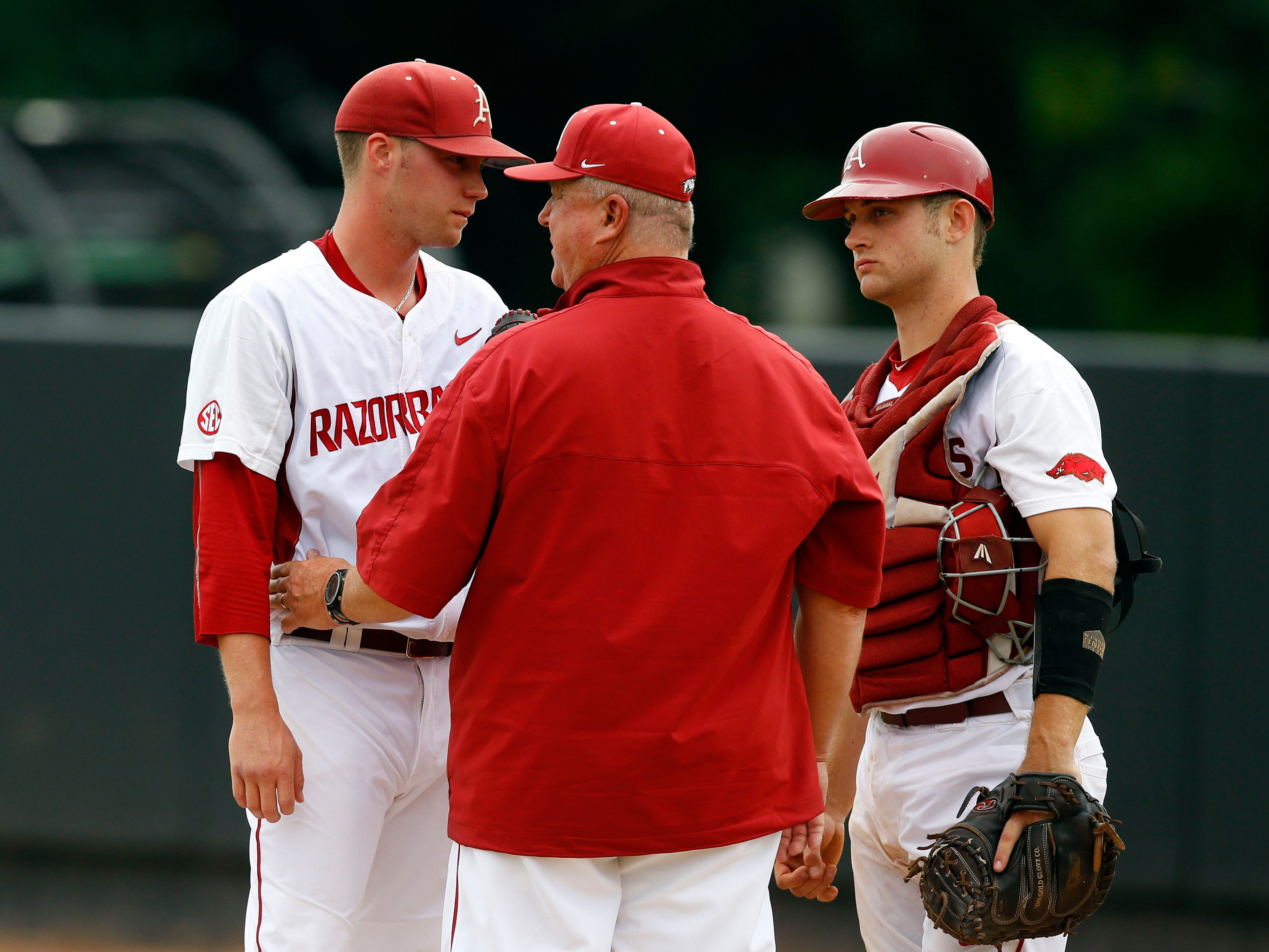 Arkansas pitching coach Dave Jorn, center, talks with starting pitcher Trey Killian and catcher Tucker Pennell in the first inning of a game against Oral Roberts at the Stillwater Regional of the NCAA college baseball tournament in Stillwater, Okla., Friday, May 29, 2015. (AP Photo/Sue Ogrocki)