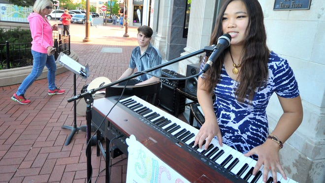 Katherine Plier, right, and Corbin Bullard, play some tunes during Thursday's inaugural kickoff of First Thursdays in downtown Wausau.