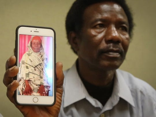Abaker Mohamed, a refugee from Sudan, holds a photo of his mother, who was killed during the war in Darfur.