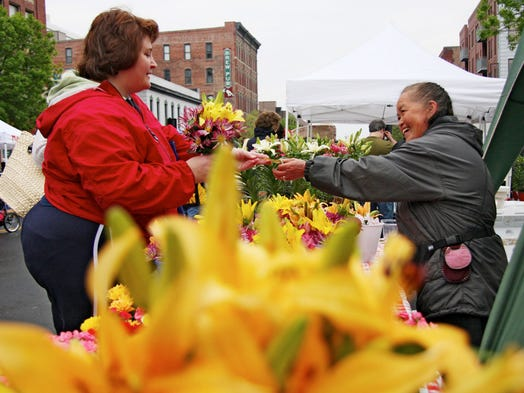 Sheila McLaughlin of Des Moines, buys flowers from Xay Lee of Ankeny who has been a vendor at the Downtown Farmers Market for 25 years.