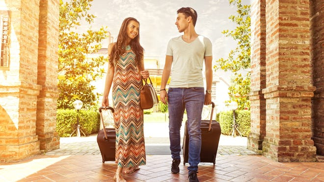 A young couple walking through a hotel portico with wheeled suitcases