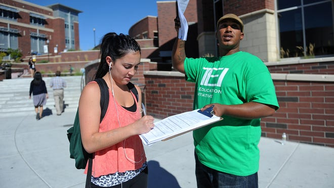 Petitioner Craig Morgan, right, collects a signature from University of Nevada, Reno student Katherine Garcia for a margins tax petition last year on the University of Nevada, Reno campus.