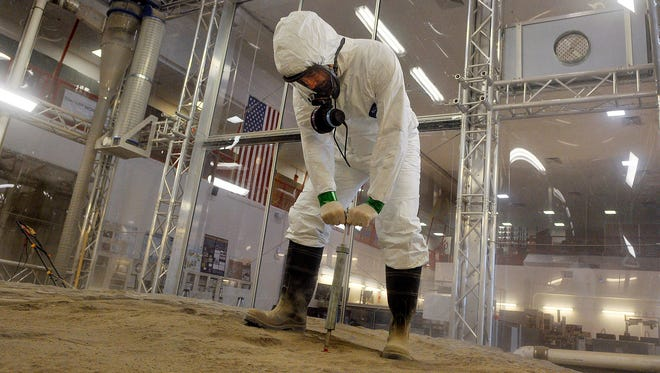 Philip Metzger, a NASA physicist and lab manager for the Granular Mechanics and Regolith Operations Lab, runs tests on sand from Black Point, Ariz., in the Regolith Test Bin at Kennedy Space Center. The lab simulates a lunar surface and is believed to be the largest of its kind.