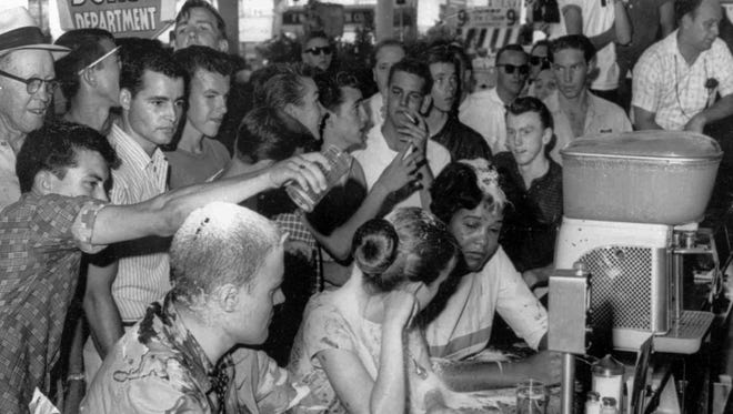 In this May 28, 1963, photograph, a group of whites pours sugar, ketchup and mustard over the heads of Tougaloo College demonstrators during a sit-in at a Woolworth's lunch counter in Jackson, Miss. Seated at the counter, from left, are Tougaloo College professor John Salter and students Joan Trumpauer and Anne Moody.