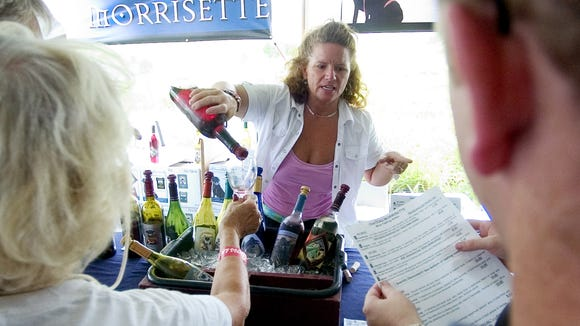 Donna Kern pours wine for Ch?teau Morrisette at the Daylily and Wine Festival in Fishersville on Saturday, July 15, 2006.