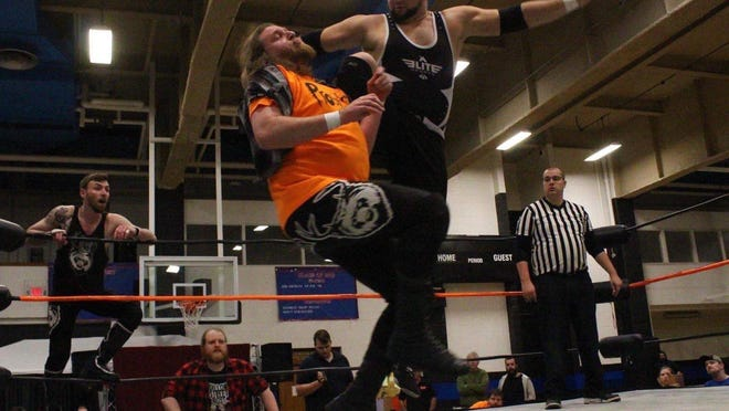 Adam Constable (as Adam Stone) rings an opponents bell with a high knee strike.