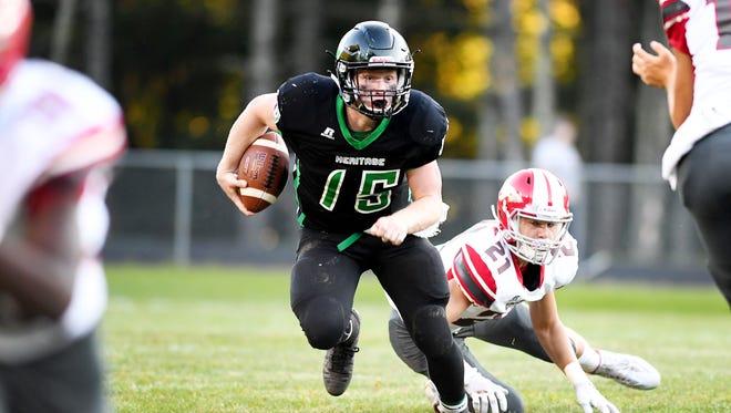 Mountain Heritage's quarterback, Trey Robinson, gets by Erwin's Tristian Brank in Burnsville August 24, 2017. Mountain Heritage won, 51-13.