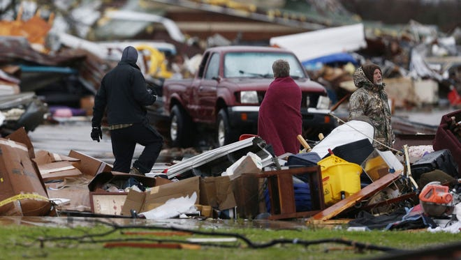 People assess the damage to a storage facility destroyed by a tornado in Garland, Texas, Dec. 27, 2015. (Nathan Hunsinger/The Dallas Morning News via AP)