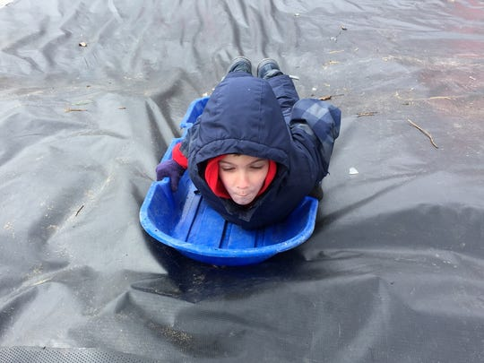 Hayden Vanvalkenburgh, 6, sleds down a hill covered with a tarp at Camp Cavell on Saturday.