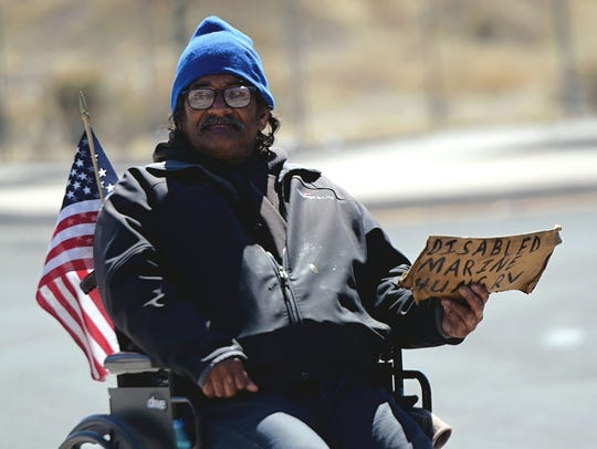 Jesse Hernandez, 60, sits in a wheelchair on a traffic