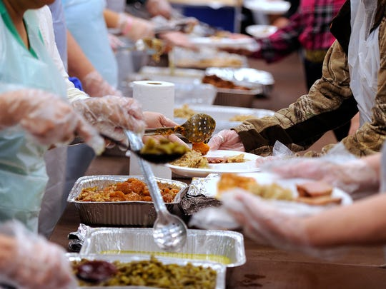 Volunteers pile food on to plates in the serving line during the Veterans Service Office's Operation Thanksgiving meal on Thursday, Nov. 24, 2016, at the Abilene Civic Center.