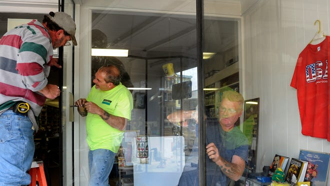 Kevin Wigal, Wes Hancock, and Jeff Wickham, of Blake Brothers Glass Company, install a new window at Newark Family Shoe Store on Thursday afternoon. The business, located on the square in downtown Newark, was broken in to overnight.