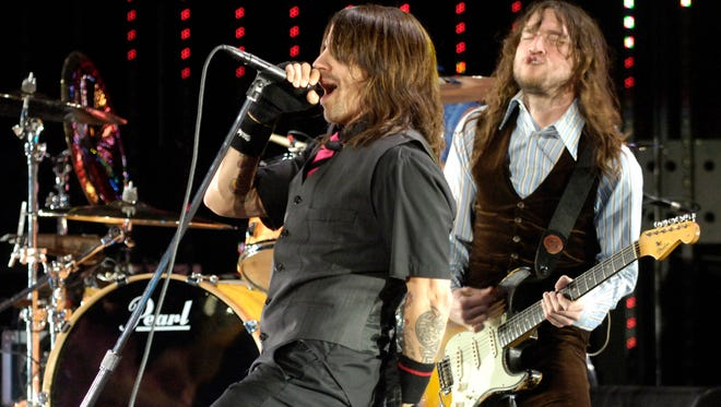 Anthony Kiedis, left, and guitarist John Frusciante of the Red Hot Chili Peppers perform on May 13, 2006. Frusciante left the band in 2009, but now he's back.