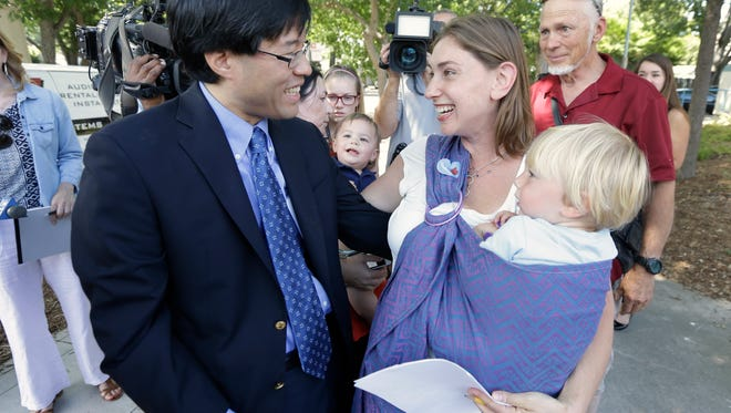 Sen. Richard Pan, D-Sacramento, is thanked by Leah Russin, holding her son Leo, 21 months, after Pank's measure requiring nearly all California school children to be vaccinated in response to a measles outbreak in Disneyland last year, was signed by Gov. Jerry Brown, Tuesday, June 30, 2015, in Sacramento,Calif.  The bill, SB277, gives  California one of the toughest vaccination laws in the country. (AP Photo/Rich Pedroncelli)