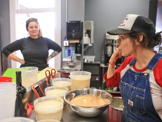 Master baker Dylan Sortman looks on as Hi-Five Doughnut store co-owner Leslie Wilson tastes a sweet and spicy glaze inside the doughnut store's kitchen Monday. The popular food-truck doughnuts will be available five days a week in a store setting on Main Street in Butchertown.