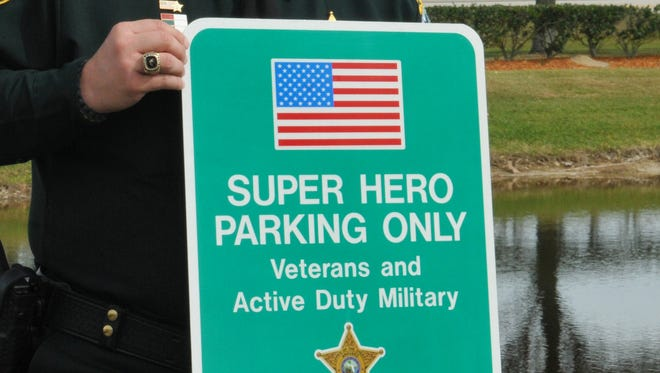 A way of saying thanks. Brevard County Sheriff Wayne Ivey shows the new Super Hero parking space signs for veterans and active duty military, should they choose to use them.