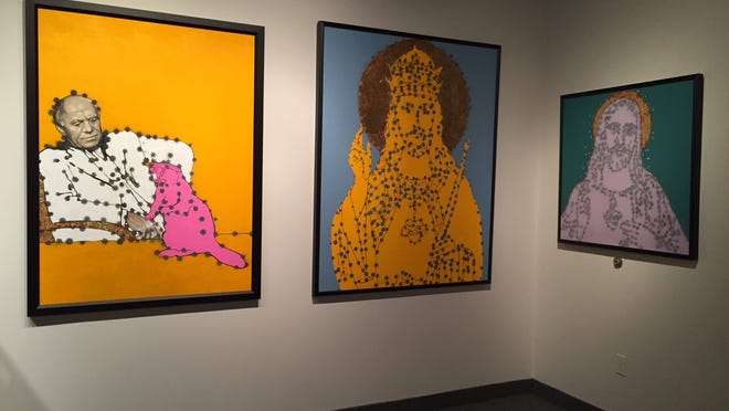 Some of Viktor Mitic's art, created with paint and guns, hanging in the ARTISANworks gallery.