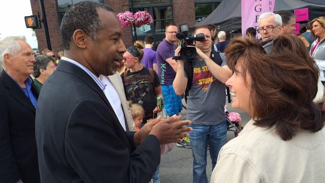 Ben Carson meets Denise Colgan of West Des Moines at the Downtown Farmers' Market in Des Moines Saturday.