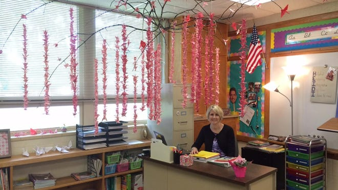 """Sunrise Elementary fourth-grade teacher Heidi Richard sits among the cranes that were made for her by T.J. Walker Middle School sixth-grade students. T.J. Walker Middle School teacher Kasee Jandrin got the idea for the cranes from the book """"Sadako and the Thousand Paper Cranes"""" by Eleanor Coerr."""