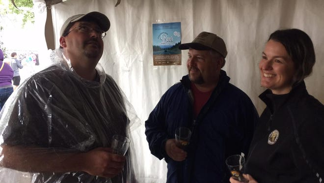 Mike O'Rourke, left, and his wife, Lisa O'Rourke, of Minneapolis, and Sean O'Rourke, center, of Sacramento, California, stand under a tent Saturday at the Oregon Brewers Festival in Portland.