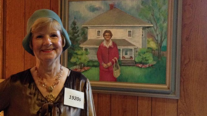Carol Crawfis wears a flapper costume from the Wayne State University vintage costume collection as part of the Franklin Community Church's 175th anniversary celebration. She stands beside the portrait of beloved church member Mildred Wood, who was a keeper of church history.