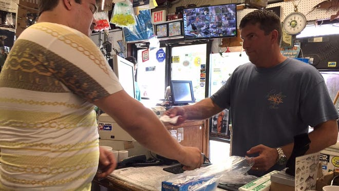 Gulf Breeze Bait & Tackle Shop General Manager Victor Wright rings up customer Daniel Lemerond on Friday morning at the store, 850 Gulf Breeze Parkway.