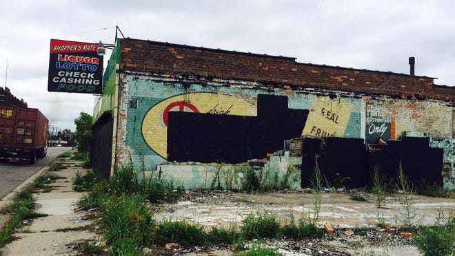 Black paint obscures a Faygo sign painted on a building that had been exposed after a neighboring structure was torn down.