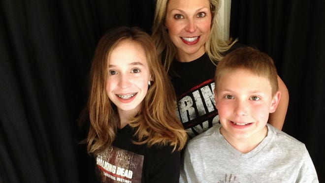 """Ericka Calcagno, center, her daughter Gina Binder, 12, left, and son Jean-Luc Binder, 9, wear T-shirts from """"The Walking Dead,"""" at their home in Farmington Hills, Michigan. Calcagno says her husband first introduced her to the series and her kids were intrigued by their conversations about it. And now they all watch the popular zombie show as a family."""
