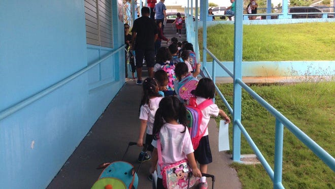 In this Oct. 15, 2015, file photo, pre-kindergarten students at Lyndon B. Johnson Elementary in Tamuning walk toward the car lane to be picked up at the end of the school day.