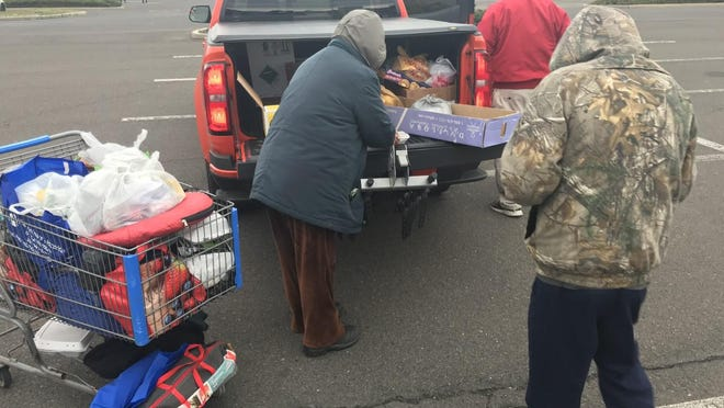 A homeless woman (left) and a homeless man (right) collect hot meals made by a local church and distributed by Advocates for the  Homeless and Those in Need in the Levittown Shopping Center parking lot on March 25. There is no Code Blue shelter this year, since CDC guidelines on social distancing  render the church halls that usually host too small.