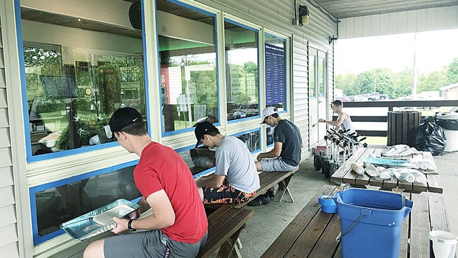Ashland High School's golf team members paint the trim and windows to finish the refurbishment of the Brookside Golf Course Clubhouse on Saturday.