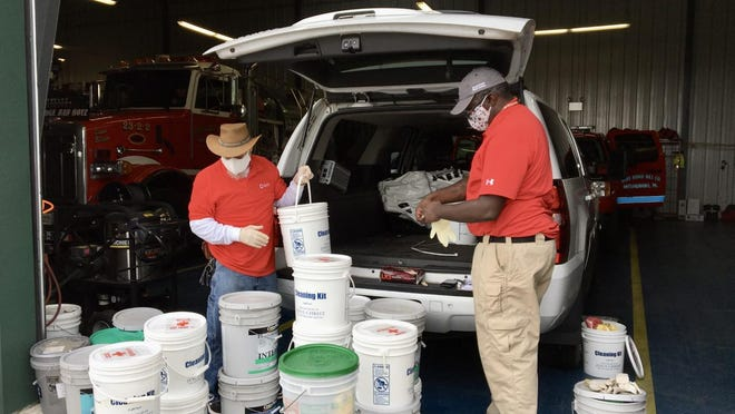 American Red Cross lead community liaison James Emmons and Monroe County disaster program specialist Donnell Riley sort out emergency supplies at Blue Ridge Hook and Ladder for the community following Tropical Storm Isaias, which caused significant flooding throughout the Poconos on Tuesday.