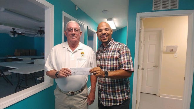 Doug Uhland, faithful navigator, is shown presenting Zeb Hough, new director of RCS, with a $2000 donation from Assembly 1820 Knights of Columbus to RCS.