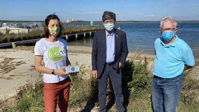 From left, C-10 Executive Director Natalie Hildt Treat, state Rep. Peter Somssich, D-Portsmouth, and C-10 member Howard Gonia across from Seabrook Station nuclear power plant. They installed a new radiation monitor at Seabrook Beach this week.