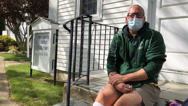 """Thomas Salamone, of Barnstable, sits outside the First Baptist Church of Hyannis. """"When you're the leader of the free world, you're the first person to put a mask on,"""" he said of his reaction to the news that President Donald Trump had tested positive for COVID-19."""