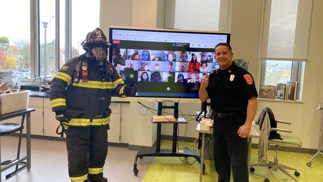 Saugus Firefighter Anthony Arone, left, and Saugus Fire Lt. Bill Cross, right, talked to Veterans Memorial Elementary School third-graders virtually about fire safety. Courtesy photo