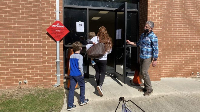 A poll worker opens the door for a woman as she prepares to vote at the First Baptist Church of Augusta precinct on Tuesday, Nov. 3 2020.